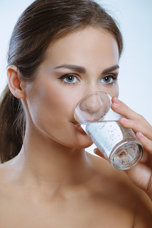 vasos de agua: Mujer joven deportiva beber agua fr�a de vidrio Foto de archivo