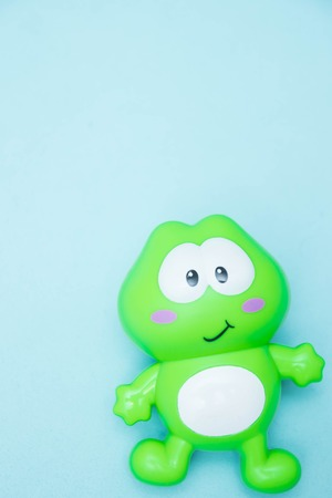 Funny green frog isolated on blue background.