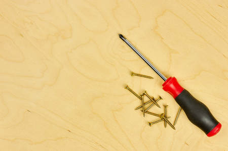 screwdriver and pliers with screws lie on the plywood. DIY concept. 版權商用圖片