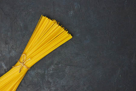 Uncooked pasta tied with a rope on concrete against black background. copy space. view from above. Banque d'images