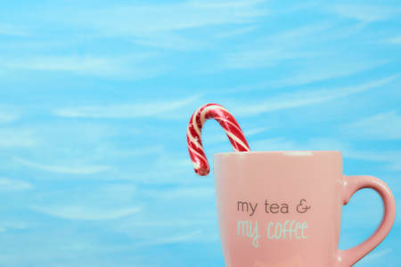 Pink Cup on blue background with coffee text. Horizontal view, copy space, pastel colors.