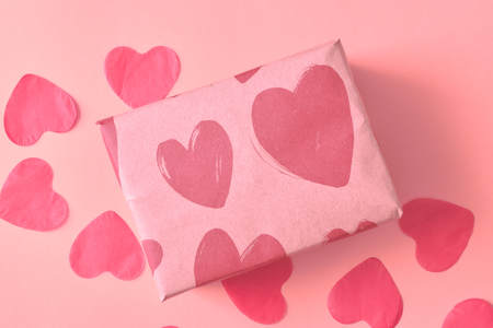 Gift in Kraft paper with red hearts on pink background with hearts. The Concept Of Valentines Day. close up.