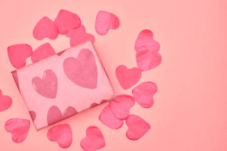 Gift in Kraft paper with red hearts on pink background with hearts. The Concept Of Valentine's Day. Stock Photo