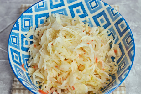 salad of pickled cabbage. Traditional Russian appetizer sauerkraut with carrots in a plate on a white wooden table. Rustic style. Selective focus and copy space