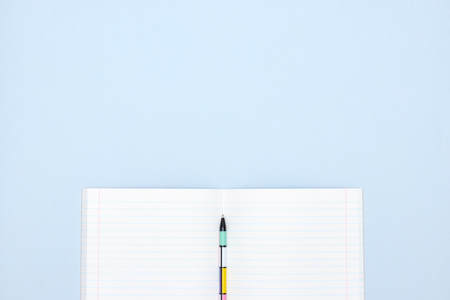 open school notebook with pen on blue background. a clean, white sheet of notebook paper for recording. Archivio Fotografico