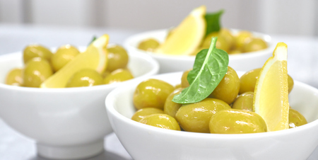 Whole green Greek olives in a white bowl. close up. vertical view of olives.