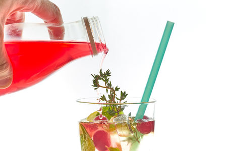 Cold mint berry cocktail in a sling isolated on white. copy space. summer refreshing drink with a straw.free space for text.