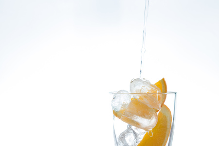 ice drink with orange and ice in the studio on a white background. a stream of water pours into