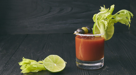 Cocktail Bloody Mary with lime and celery, salt and snacks in a glass on a black wooden table.