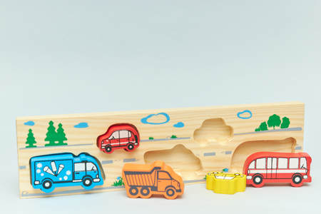 wooden retro typewriter toy on a light background. group of cars with empty space. close-up. educational toys for children.