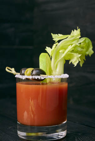 Cocktail Bloody Mary with lime and celery, salt and snacks in a glass on a black wooden table. vertical view of a cocktail. Stockfoto