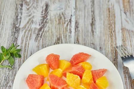 Orange-grapefruit citrus salad on a shabby wooden table. copy space. summer vitamin