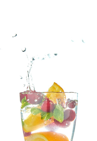 orange splashing into a glass of water with mint and berries on a white background. refreshing summer drink