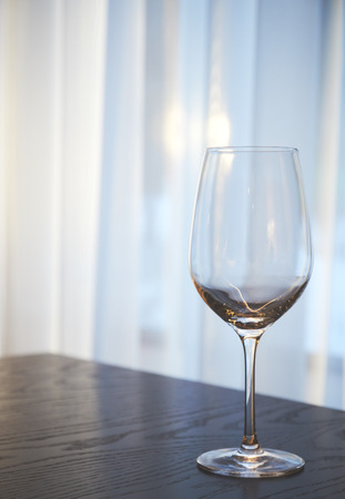 empty wine glass on a table in a restaurant. background is out of focus. interior