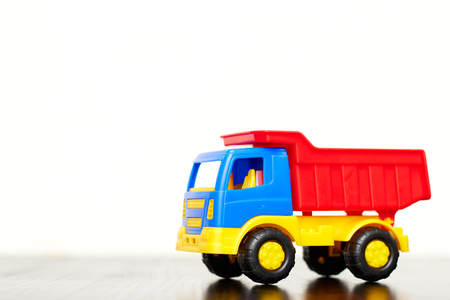 childrens toy truck, dump truck plastic multicolored on white background isolated Imagens