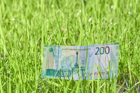 Banknote Two hundred Russian rubles. Paper Russian money on the background of green grass Imagens