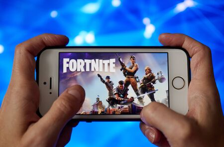 San Francisco, CA USA - April 2019: hand holding a phone with a Fortnite game logo