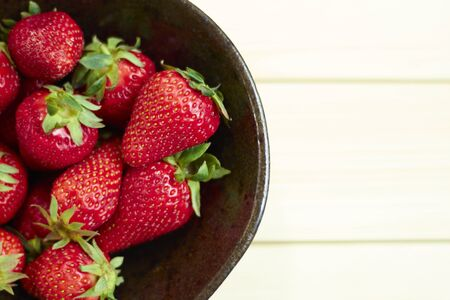 Fresh strawberries on wooden bowl. Sackcloth background. Copy writing space.