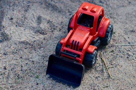 Teddy red tractor in the sand. Kids toys. toy concept for children. copy space. Stockfoto
