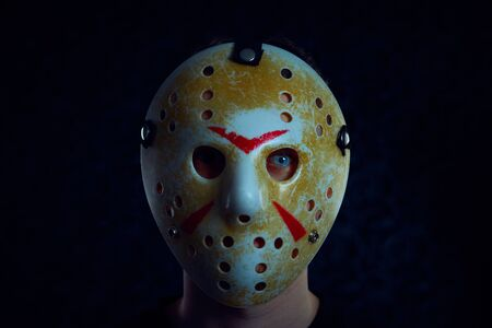 Friday 13th hockey mask of Jason Voorhees. Halloween concept. day of death. man in a jason mask on a black background.