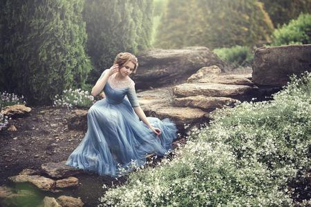 Una bella ragazza come Cenerentola sta camminando nel giardino.
