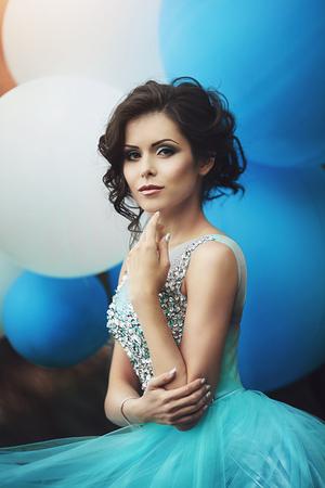 ヘリウム気球プロムの女の子。大きな青と白の風船と青いドレスで美しい少女卒業の肖像画。公園の美しいドレスでエレガントな若い女性です。ア