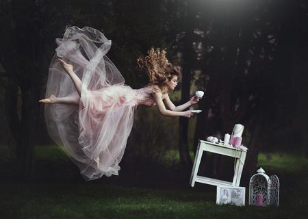 아름 다운 금발 소녀 테이블 위로 차 찻잔에 기대어입니다. 중력의 부족. 이상한 나라의 앨리스처럼. 긴 머리를 가진 여자는 동화 속에서 날아간다. 크 스톡 콘텐츠