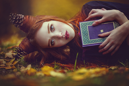 Portrait of a beautiful red-haired girl with an unusual hairdo with a book in the autumn fairy forest. A fabulous autumn photo shoot.