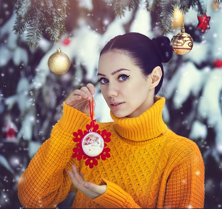 A beautiful girl with blue eyes in a yellow sweater is holding a New Years toy under a snow-covered tree. A girl in fairy-tale New Years decorations. Magic winter forest.