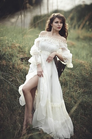 A beautiful tender girl in a white dress sits on a tree stump.