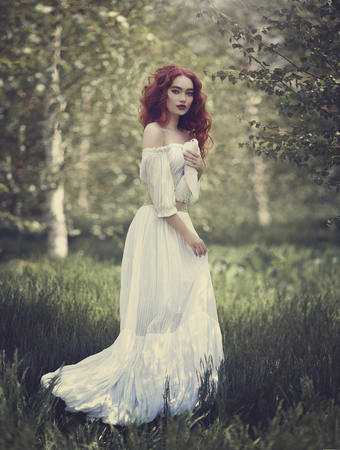A sensual red-haired girl in a white dress with bare shoulders holds a white dove in her hand. White dove is a symbol of peace.