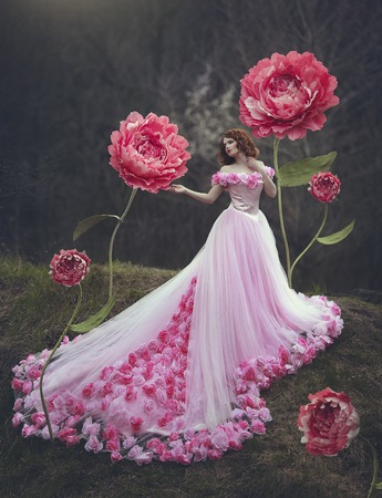 Beautiful sensual girl with red hair in a fairy pink dress with a huge train posing near the giant flowers of a pink peony. The girl is a flower princess. Stockfoto