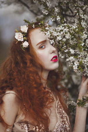 A gentle woman with long red hair in a blooming spring garden. Red sensual girl with pale skin and blue eyes with bright unusual appearance hides behind flowers.