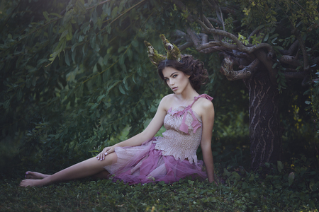 Girl enchanted Princess with horns sitting under a tree. Girl Mystical creature fawn in shabby clothes in a fairy forest. Halloween concept ideas.