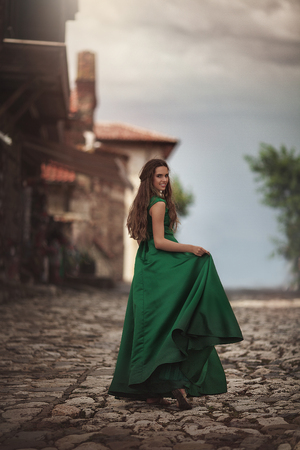 Woman in green dress on the streets of the old town. Young tourist on vacation travel smiling happy walking joyful in Italy, Europe.
