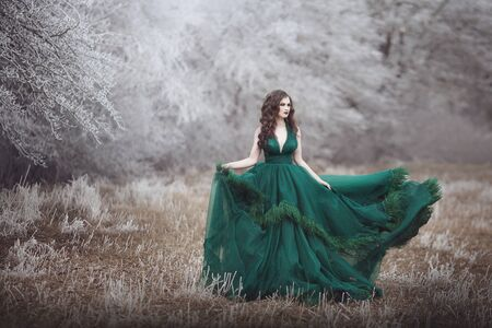 Beautiful long-haired girl in a magnificent emerald fairy dress walks in the winter forest. The wind develops hair and hem paying. Fairy tale fantasy story.