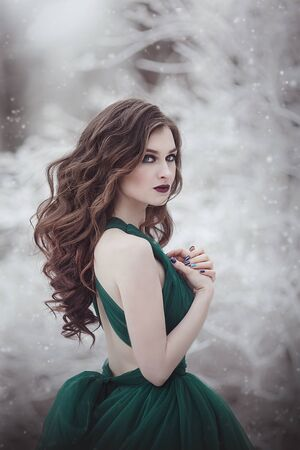 Portrait A beautiful long-haired girl in an emerald fairy dress walks in the winter forest. Fairy tale fantasy story.