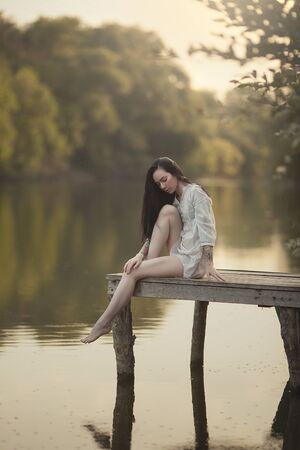 A young woman sits on the bridge by the water. Nymph girl at the lake. Stock Photo