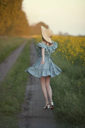 A girl in retro clothes with a straw hat runs along a rural road along a yellow field. Rear view, running away into the distance. Stockfoto