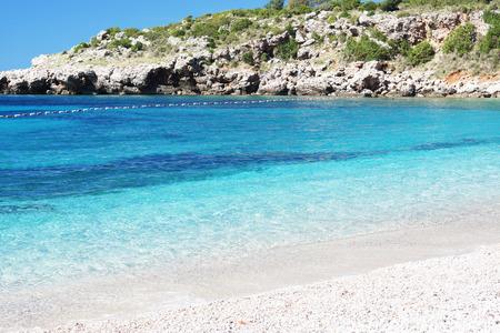 boyas: Agua clara azul en la playa con una roca, boyas de esgrima