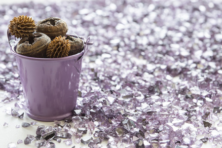 shards: Purple bucket full of dry pine cones stands among purple shards of glass Stock Photo