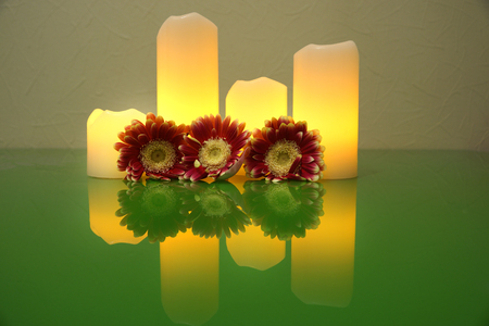 Three Gerbera flower and four lighted candles reflected in the green surface of the glass desk, Spa Style Stock Photo