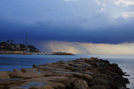 Stone pier, looking at sea, the suns rays make their way through the storm clouds, the pre-dawn twilight