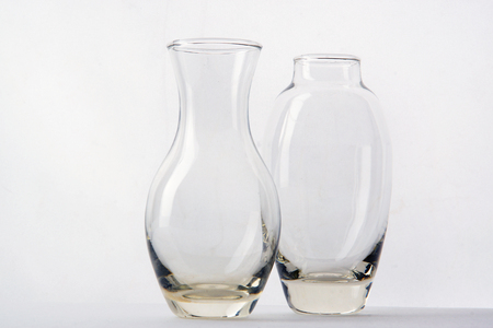Two Glass Vases Of Different Shapes Are Side By Side On A White