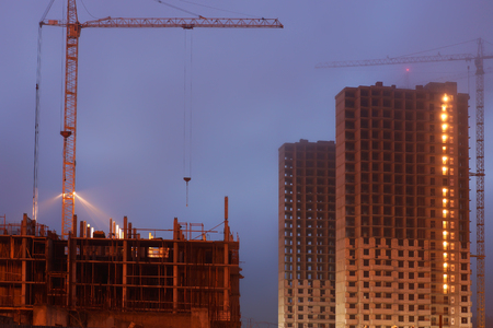 storey: Construction crane on the site, unfinished multi-storey houses, fog covers the upper floors, evening twilight
