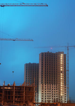Two cranes on the construction site, unfinished multi-storey house, foggy evening twilight, the lighting of the floors