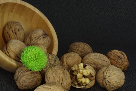 albero nocciolo: Le noci sono sparse da una ciotola di bambù su uno sfondo nero, uno è aperto, un fiore verde brillante. Salutare sano, buono per il cervello. Archivio Fotografico