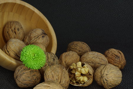 overturn: Walnuts are scattered from a bamboo bowl on a black background, one is opened, a bright green flower.Healthy eating, good for the brain.