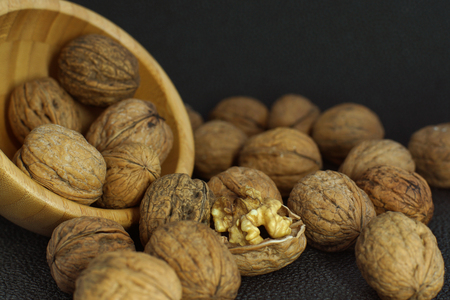 Walnuts are scattered from a bamboo bowl on a black background, one is uncovered.