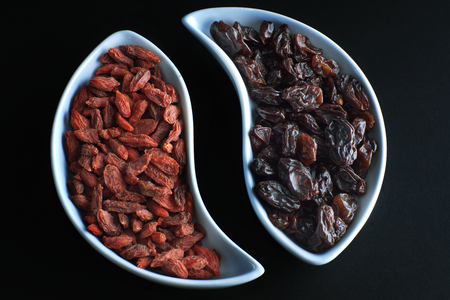 Two curved bowls with dried goji berries and grapes opposite each other on a black background. Stock Photo